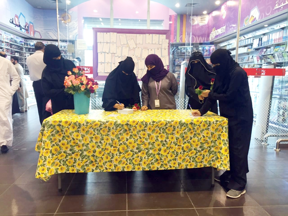 سعوديات يكتبن رسائلهن للأمهات على جدارية في أحد المجمعات التجارية في جدة بمناسبة يوم الأم. (عكاظ)
