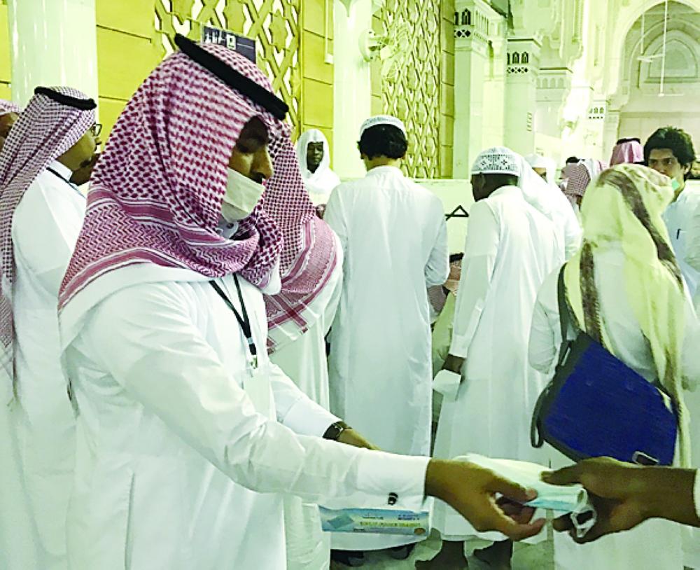 موظفو الرئاسة يوزعون الكمامات على الزوار.  (عكاظ)