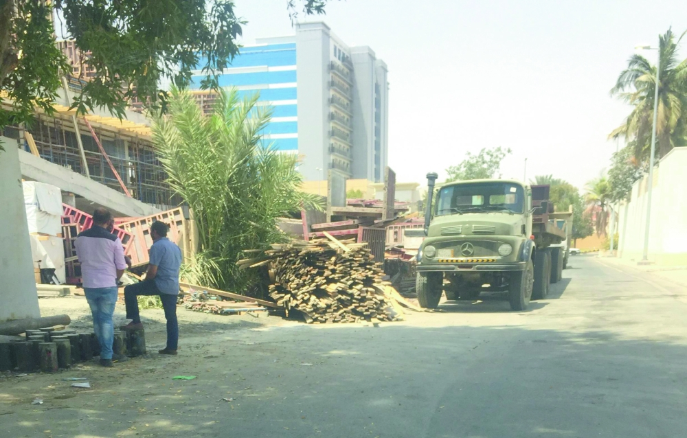 شاحنة تفرغ الأخشاب في حي الروضة. (عكاظ)