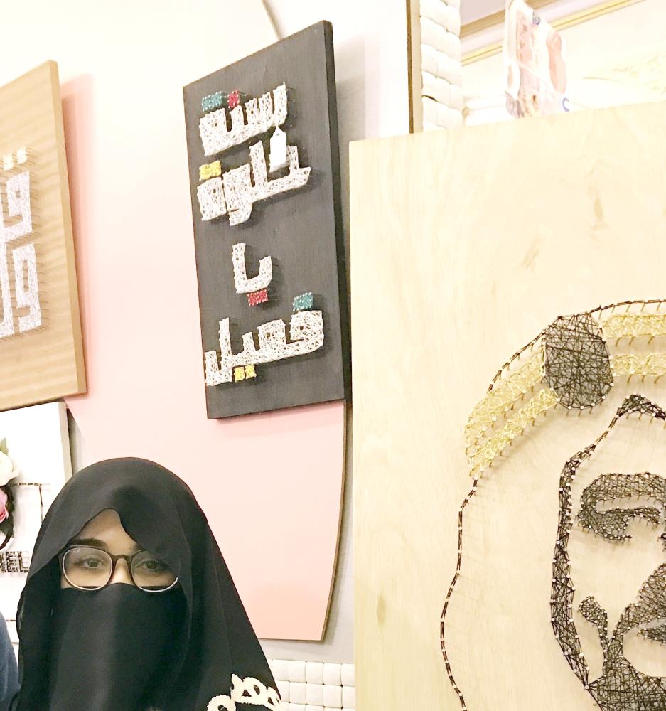 الفنانة أهداب سقطي مع بعض أعمالها.   (عكاظ)