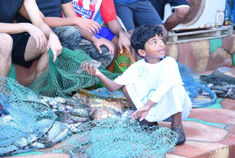 طفل تبدو عليه علامات الفرح وهو يمسك بإحدى الأسماك. (عكاظ)