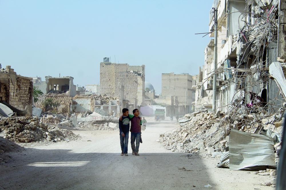 طفلان هائمان في مدينة الباب في ظل الدمار.